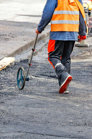 A road service worker who measures road distances with a measuring wheel determines the required amount of asphalt for paving. Vertical image, copy space.