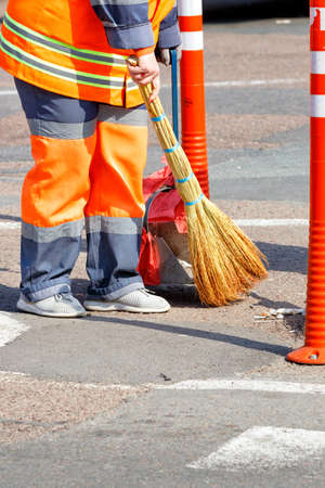A female janitor in bright orange uniforms sweeps the street by a fence of orange road columns. Vertical image, copy space.
