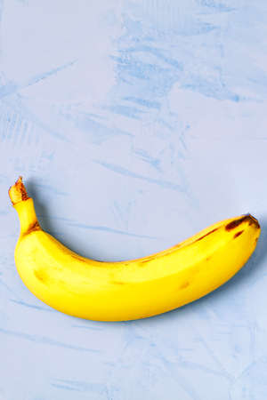 A ripe yellow banana in the lower third, against a blue plaster background, resembles a smiley. Vertical image, flat lay, copy space. Reklamní fotografie
