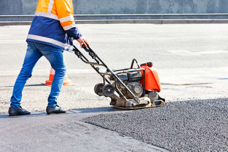 A road service worker repairs a section of the road on a sunny day, compacting fresh asphalt with a vibrating plate. Copy space.