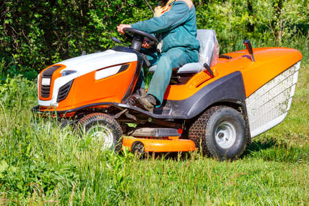 A gardener sitting at a professional tractor lawn mower mows tall green grass in an overgrown meadow on a clear sunny day. Copy space.