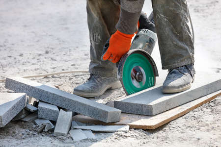 A builder's hands are strenuously cutting granite blocks in a cloud of dust with a diamond saw in front of the workplace Close-up, selective focus, copy space. 免版税图像