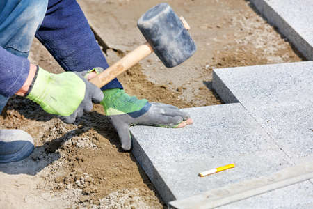 A worker in a blue overalls, half crouching, knocks with a rubber hammer on granite blocks, assembling a new sidewalk. Close-up, selective focus, copy space.