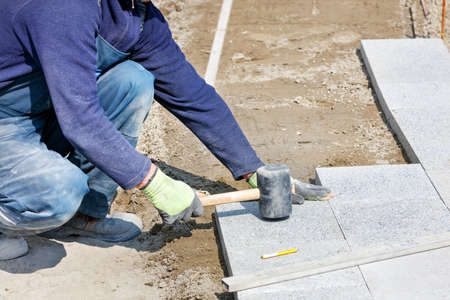 A worker in a blue overalls, half-crouched, strikes the granite blocks with a rubber mallet, assembling a new sidewalk onto the sandy base of the marked area. Close-up, selective focus, copy space.