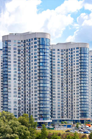 White and blue rounded facades of new residential high-rise buildings in a residential area of the city on a summer day against the backdrop of a blue cloudy sky. Vertical image, copy space.
