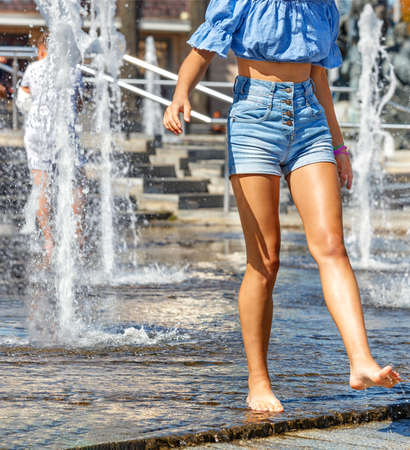 Beautiful figure and legs of a young girl walking barefoot among the high jets of the city fountain and refreshing water on a hot summer day. Vertical image, copy space.