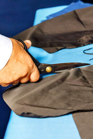 A tailor makes a pattern out of black fabric with his hand using old tailor's scissors. Vertical image, close-up, copy space.