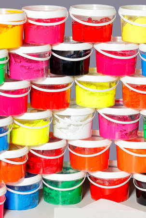 Screen printing inks in a variety of vibrant colors are stacked in clear plastic containers on top of each other. Vertical image.