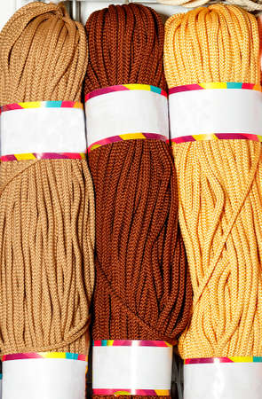 Rolls of polyester cord in various colors of brown and beige shades, rolled. Vertical image, close-up, copy space. 免版税图像