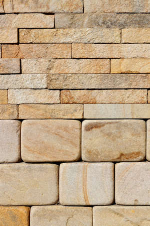 Wall background and texture, stacked with rounded yellow sandstone at the base and rough rectangular tiles at the top. Vertical image, close-up, copy space.