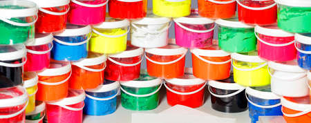 Screen printing ink in a variety of bright colors is laid out in a panoramic semicircle and stacked in transparent plastic containers. 免版税图像