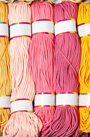 Rolls of polyester cord in various colors of pink shades, rolled into a roll. Vertical image, close-up, copy space.