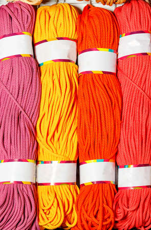 Rolls of bright pink, red, yellow and crimson polyester cord, rolled. Vertical image, close-up, copy space. 免版税图像
