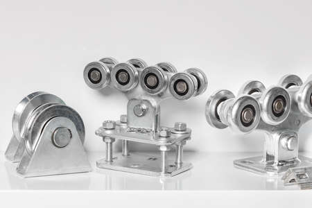 Steel special roller bearing mechanisms with a strong metal platform for moving heavy loads. Light background, close-up, copy space.
