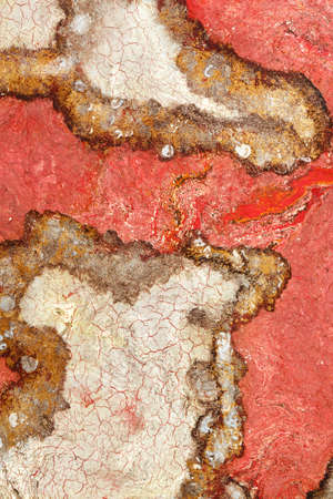 Fiery red texture of red granite with brown and beige fractals and cracks. Polished surface. Vertical image, copy space. 免版税图像