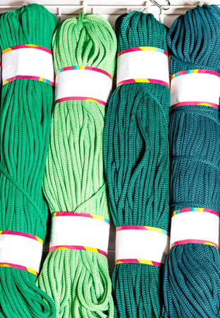 Rolls of polyester cord in various vibrant shades of green, rolled. Vertical image, copy space.