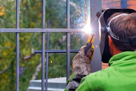 A bright flash from an electrode when a welder works to install a metal fence around a house against a blurred background of a green park.