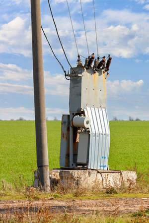 An old transformer station with bare wires stands near a concrete pole and a green agricultural field against a blue cloudy sky. Vertical image, copy space.
