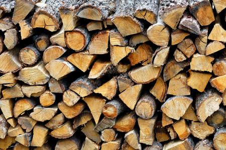 The texture of coarsely cut and neatly stacked oak firewood, natural texture.