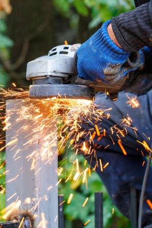 Lots of hot sparks are thrown off as the craftsman works by cutting the metal post with a disc angle grinder. Vertical image, selective focus, copy space.