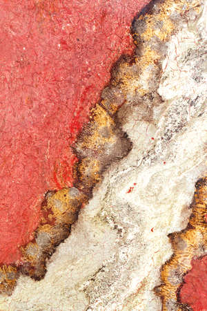 Unusual texture of red granite with brown and beige streaks and cracks. Vertical image, copy space.