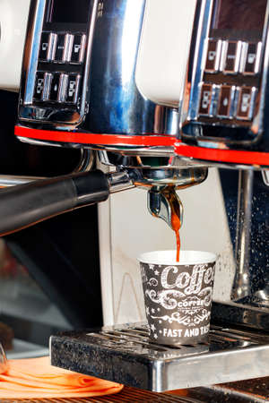 The coffee machine pours aromatic coffee into a cardboard cup. Vertical image, copy space.