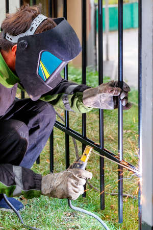 A welder in protective clothing, a helmet and leather gloves, using an electrode, welds a metal fence, installs a fence. Vertical image, selective focus, copy space.