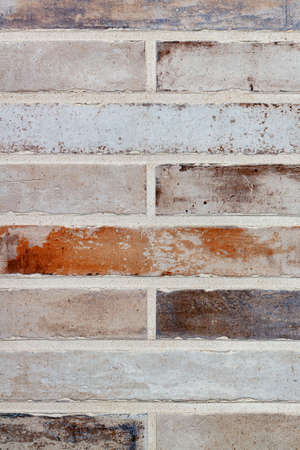 Texture and background of a wall made of old long bricks in the form of brickwork with even symmetrical cement joints. Vertical image, copy space.