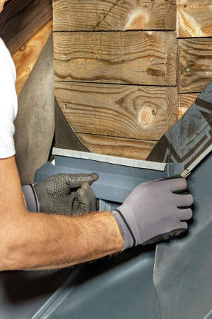 The worker mounts a waterproof bitumen membrane with screws for waterproofing the chimney when installed on the roof. The hands of an experienced rooftop technician. Vertical image, copy space.