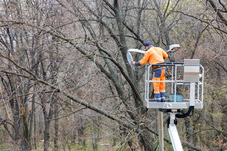 A utility worker in an orange uniform uses a construction hoist to repair street lighting on a pole against the trees in the park. Copy space.