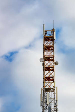 Telecommunication tower of satellite and cellular communications 3G, 4G and 5G with antennas against the background of a blue cloudy sky. Vertical image, copy space. 免版税图像