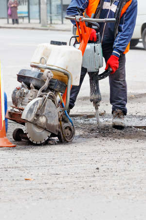 A road worker in reflective clothing on a fenced-in section of road repairs a roadway using an electric jackhammer and a gas cutter. Vertical image, copy space.