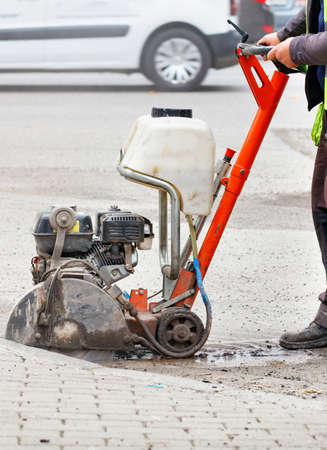 A road worker in a reflective vest cuts old asphalt on the road in front of a city street with a gasoline cutter in a blurred view. Vertical image, copy space.