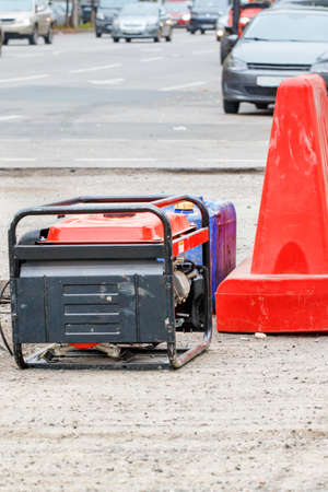 An electric generator and a canister of gasoline on a fenced work area of a road being repaired. Vertical image, copy space. 免版税图像