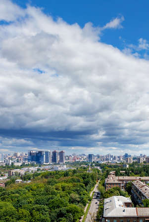 View from a height of the city of Kiev in the summer at noon. A green park in the foreground in an old residential area and new buildings on the horizon against a blue sky with an overhanging white and gray cloud. Vertical image, copy space. 免版税图像