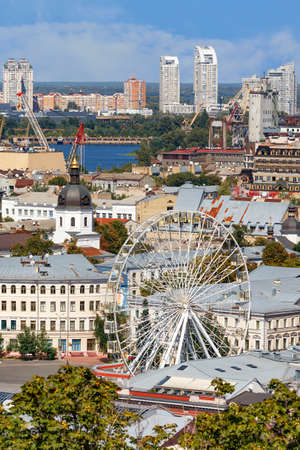 Summer cityscape of the old Podil district of Kyiv, with a Ferris wheel and a bell tower with a copper roof and a gilded dome, the Dnipro River and many city buildings. Vertical image, copy space. 免版税图像