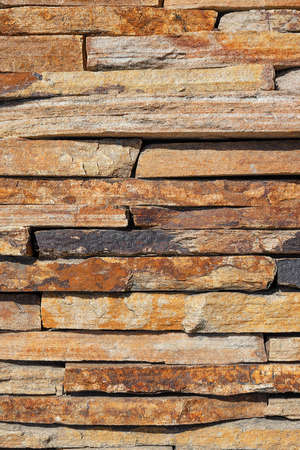 Beautiful texture of brown old sandstone stone on the wall close-up. Vertical image, copy space.