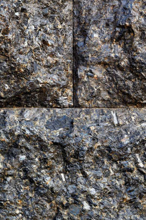 Beautiful texture of black granite blocks tightly adjacent to each other with a conditional division of the image into parts. Vertical image, copy space.