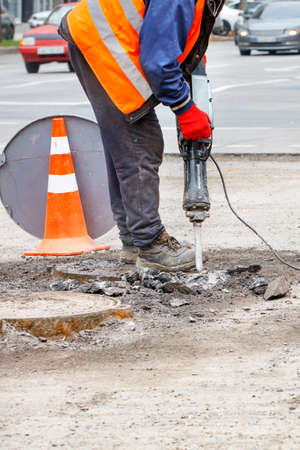 A road worker in reflective clothing works with a jackhammer on the carriageway, smashing old asphalt around sewers. Vertical image, copy space.