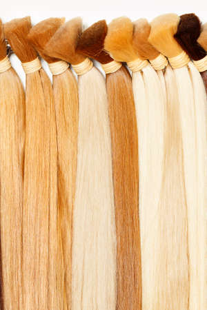 Bundles of natural healthy human hair in wheat shades. Hair care, style and beauty for women. Vertical image, copy space.