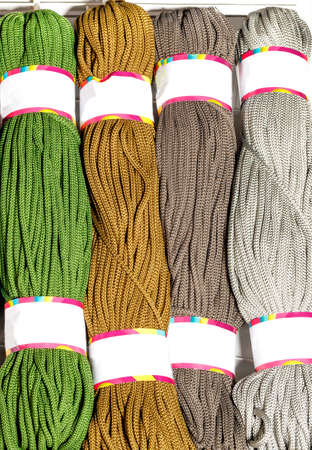 Rolls of polyester cord in various vibrant colors of green, brown and gray, rolled. Vertical image, close-up, copy space. 免版税图像