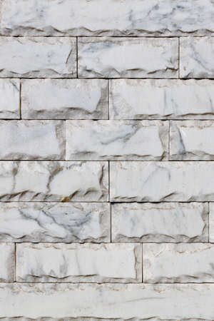 The texture of a wall covered with gray marble tiles with chips around the perimeter, brown veins on the surface and spots. Vertical image, copy space.
