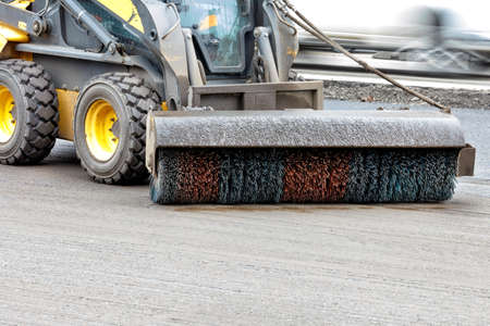 A trailed hydraulic nylon brush on a compact bobcat cleans dirt from the road. Copy space.
