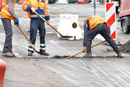 Traffic workers in bright orange reflective vests shovels road debris at the joints of the road sections being repaired. Copy space.