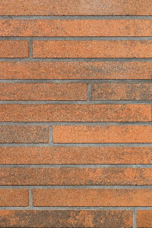 The decorative surface of the wall is brown with a horizontal brown striped surface and imitation of brickwork. Vertical image, copy space.