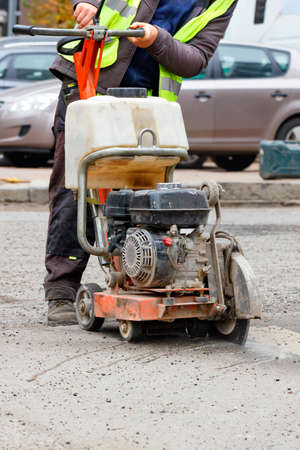 A road worker in a light green reflective vest cuts old asphalt with petrol cutter on the road against the background of a city street in blur. Vertical image, copy space.