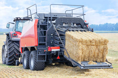 During harvesting, a tractor forms sheaves of straw into dense briquettes in a wheat field. Close-up, copy space.