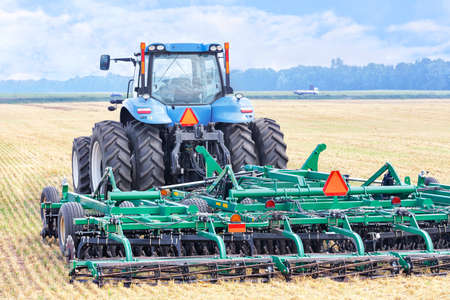 An agricultural tractor with a hitch, a harrow, stands against the background of a harvested wheat field on a summer day. Copy space.