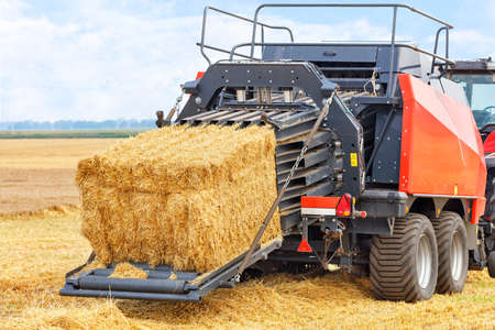 During harvesting, a tractor in a wheat field forms sheaves of straw into dense briquettes using a trailed unit. Close-up, copy space.