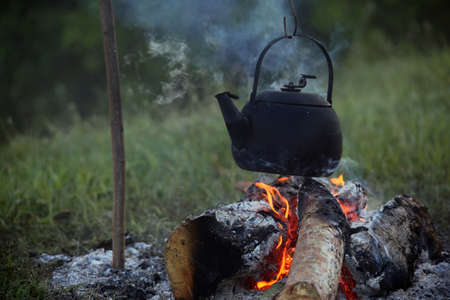 sooty: Sooty teapot boils and streaming on the bonfire at early spring morning